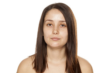 Portrait of young serious woman without makeup on white background