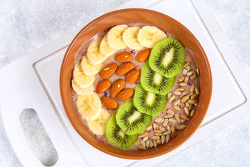 Breakfast berry smoothie bowl topped with bananas, berries, kiwi, almonds and sunflower seeds.