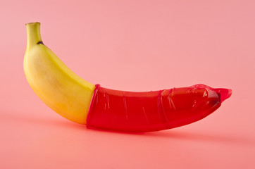 Banana with a red condom on a pink background. Safe sex concept