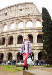 young little happy sunny girl in pink pants and glasses is standing fashion and posing on Colosseum background in Rome and smiling