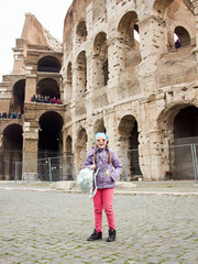 young little happy exciting girl in pink pants and glasses is standing fashion and posing on Colosseum background in Rome and smiling