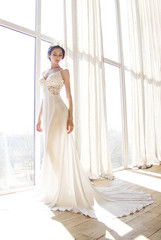 young brunette sexy girl in a white wedding boudoir dress and gold crown in hairstyle is standing like queen princess on a white window background