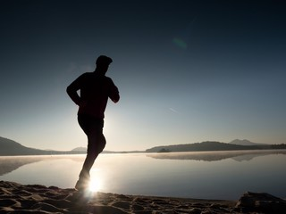 Tall fit man running fast by the sea on the beach. Powerful runner training outdoor in summer morning.