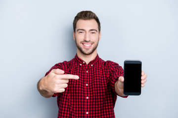 Satisfied client is showing smartphone with replaced glass. Portrait of excited glad satisfied amazed wearing checkered red shirt guy pointing on dark phone in hand, isolated on gray background