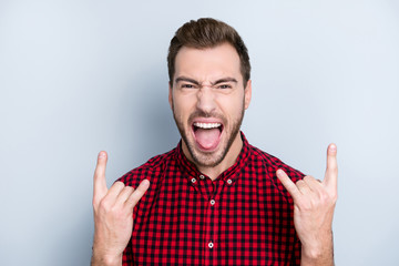 I adore heavy metal! Close up portrait of excited crazy mad cool serious guy making horns using his hands wearing casual checkered shirt and showing tongue, isolated on gray background