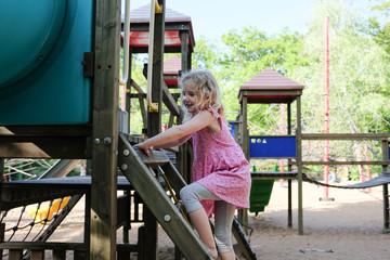 blondes mädchen beim klettern auf spielplatz