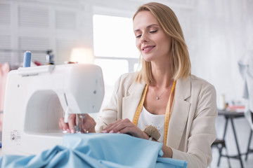 Professional tailor. Appealing female tailor using sewing machine and looking down
