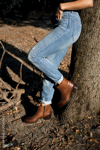 6433e76fece8b Brown shiny leather womens chelsea boots on woman legs with blue jeans in autumn  forest or