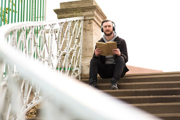 A handsome young hipster man sitting on the stairs and reading a book.