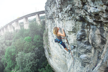 woman rock climber climbs on the cliff