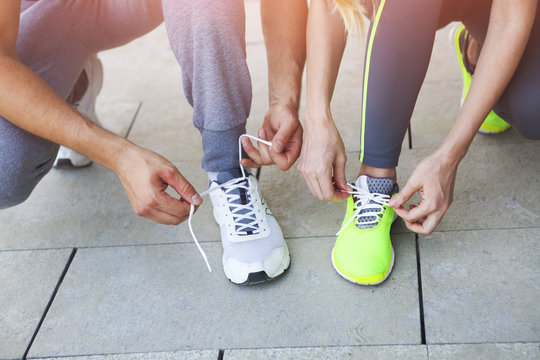 Woman and man lacing running shoes before workou