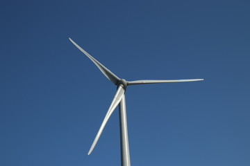 Windturbine in close-up with blue sky as background in the Netherlands.