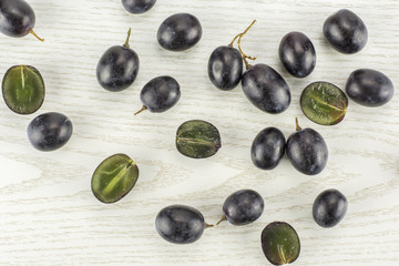 Black grape berries (autumn royal variety) table top isolated on grey wood background some sliced.