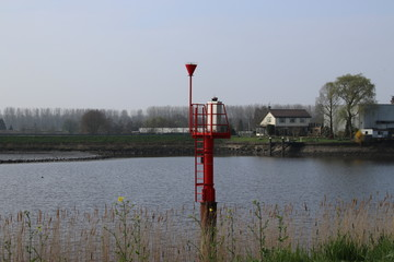 red naviagion light tower in the river Hollandse IJssel at NIeuwerkerk, the netherlands.
