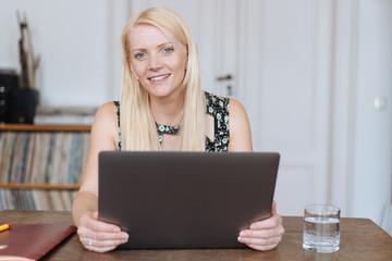 Portrait of smiling blonde woman using laptop