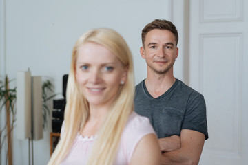 Man and blonde woman standing in domestic room