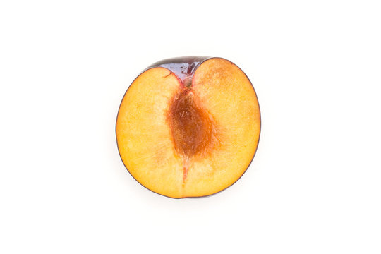 One red blue plum half top view isolated on white background cross section.