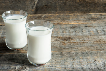Fresh healthy milk in glass cups on wooden rustic background