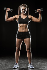 Fitness girl with dumbbells on a dark background isolated