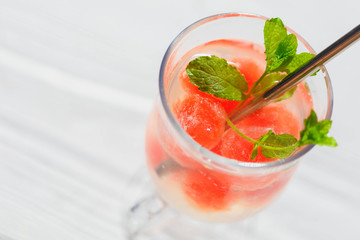 Frozen watermelon balls in a glass of mineral water with beautiful shadows, refreshing drink, clean eating,balance and healthy food and diet  concept