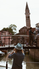 Back view of young girl taking photo at bell tower on the island of Burano in the Venice lagoon - Italy.