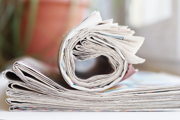 Stack of newspapers. Folded papers stacked in a pile with rolled journal on top. Concept for news and information
