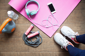 High angle view of sporty woman with fitness equipment and smartphone on wooden floor, Diet and fitness