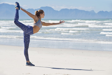 Woman In Sportswear Stretching Before Exercising On Beach In South Africa