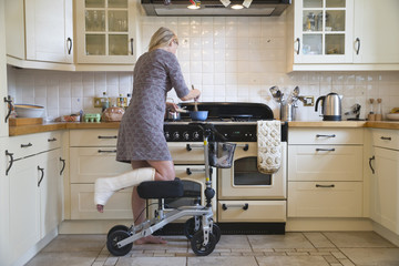 Woman With Leg In Plaster Cast At Home Using Mobility Aid Whilst Cooking Meal