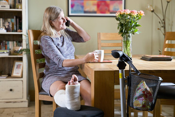 Mature Woman With Leg In Plaster Cast Sitting By Table At Home Talking On Phone