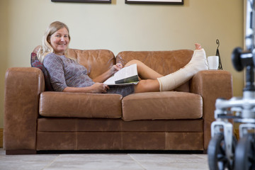 Portrait Of Mature Woman With Leg In Plaster Cast Lying On Sofa At Home