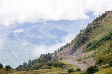 Photo of mountain slopes with vegetation and cloudy sky