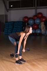Female performing deadlift exercise with weight bar. Confident young woman doing weight lifting workout at gym