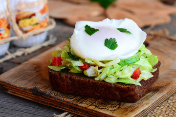 Poached egg toast sandwich. A poached egg on a rye bread slice with coleslaw, cucumber, red pepper and fresh parsley. Quick and easy healthy food. Wooden background. Rustic style. Closeup