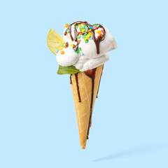 Ice cream in a horn with lime, mint and chocolate topping on a blue background.