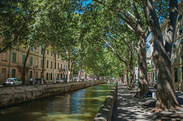 Avenue with sidewalk full of trees, canal to the center and a sunny blue sky, in the city center of Nimes. Located in the Gard department, Occitanie region in southern France