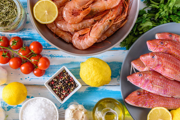 Fresh shrimps and red mullet fish on blue wooden background with herbs and spices. Flat lay.