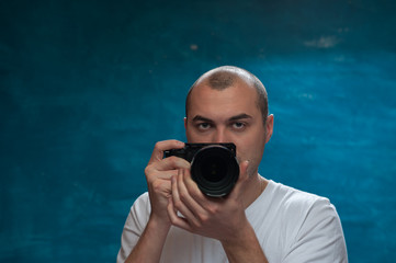 Male professional photographer posing with camera against blue background