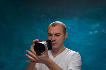 Portrait of serious middle-aged man in white shirt with camera in his hands making photos on blue background. Copyspace