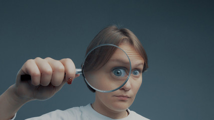 portrait of caucasian wooman with magnifier makes fun faces magnifier to the eye. Zoom, searching concept, curiocity