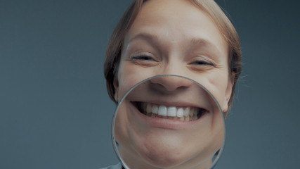 portrait of caucasian wooman with magnifier makes fun faces. Magnifier to the mouth