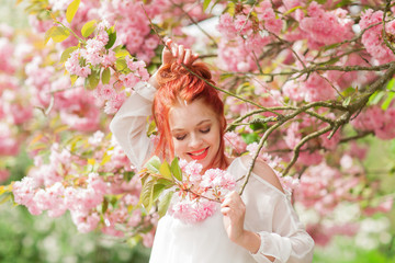 Beautiful young woman with red hair having fun standing in cherry blossom tree, springtime garden mood