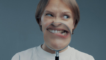 portrait of caucasian wooman with magnifier makes fun faces. Magnifier to the mouth. Woman nervious bite lips