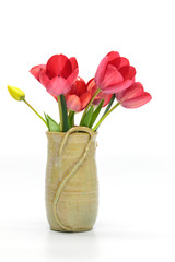 Beautiful red tulips in a rustic clay vase on white background