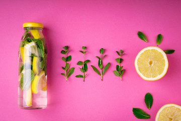 Detox fruit infused water, citrus fruits and mint leaves on pink background. Top view, flat lay, copy space