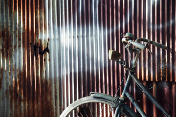 old classic bicycle with grunge rusry corrugated wall background.