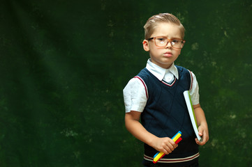 Cheerful little boy in glasses with fashionable styling in formal attire holding pens on dark green background