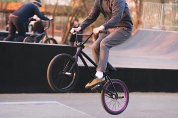 Bmx rider makes tricks on BMX in a skateboard. Evening training at Bmx. A cyclist travels on the rear wheel. Bmx Concept