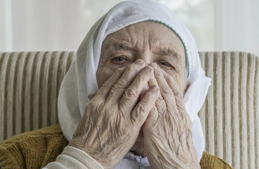 A sad senior woman praying