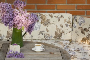 Green vase with Lilac flower, candle light and cup of porcelain coffee  on wooden table at the outdoor garden